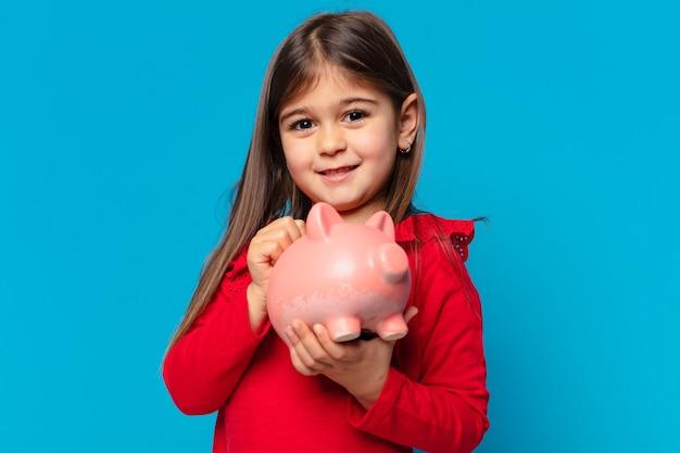Całkiem mała dziewczynka szczęśliwa ekspresja i trzymająca skarbonkę