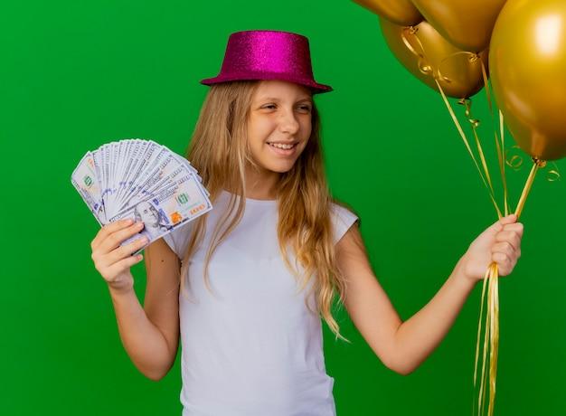 Całkiem mała dziewczynka trzyma pieniądze w świątecznym kapeluszu