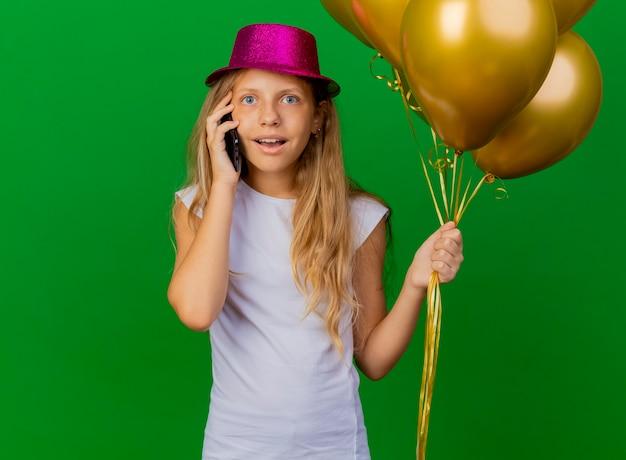 Całkiem mała dziewczynka trzymając smartfon w świątecznym kapeluszu