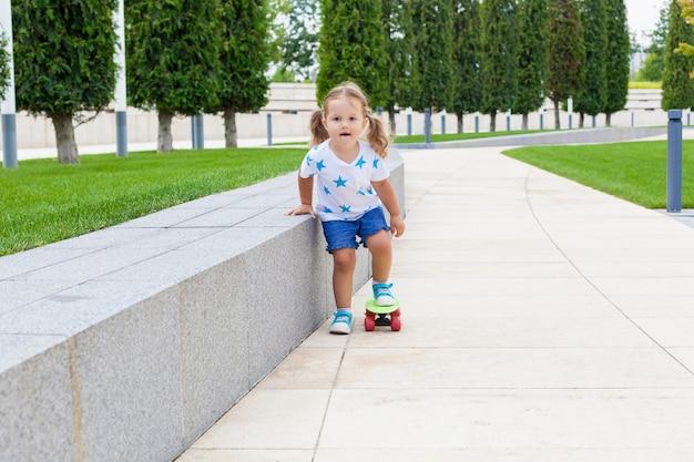 Całkiem mała dziewczynka uczy się jeździć na deskorolce