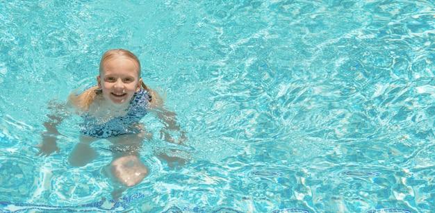 Całkiem mała dziewczynka w basenie, letnie wakacje.