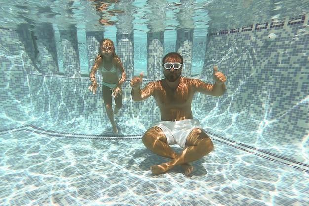 Całkiem mała dziewczynka w basenie pod wodą, letnie wakacje.