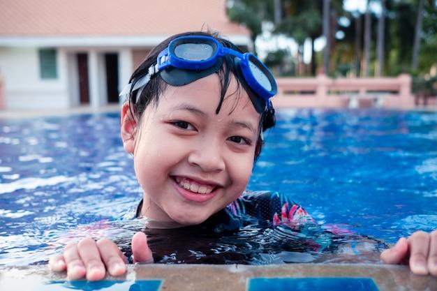 Całkiem mała dziewczynka w basenie z uśmiechem i szczęśliwy w okresie letnim