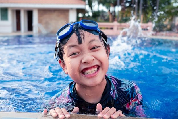 Całkiem mała dziewczynka w basenie z uśmiechem i szczęśliwy