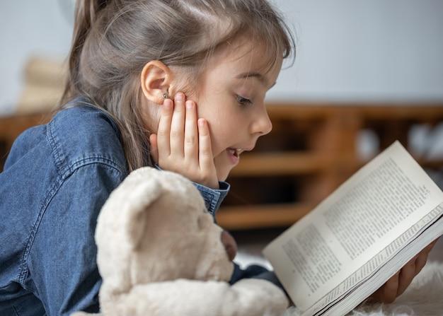 Całkiem mała dziewczynka w domu, leżąc na podłodze ze swoją ulubioną zabawką i czyta książkę.