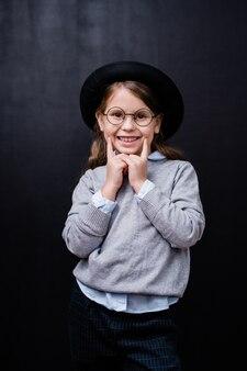 Całkiem mała dziewczynka w eleganckiej odzieży codziennej i okularach, patrząc na ciebie z uśmiechem toothy, stojąc przed kamerą