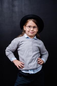 Całkiem mała dziewczynka w eleganckiej odzieży codziennej i okularach stojących przed kamerą przeciwko czarnej przestrzeni