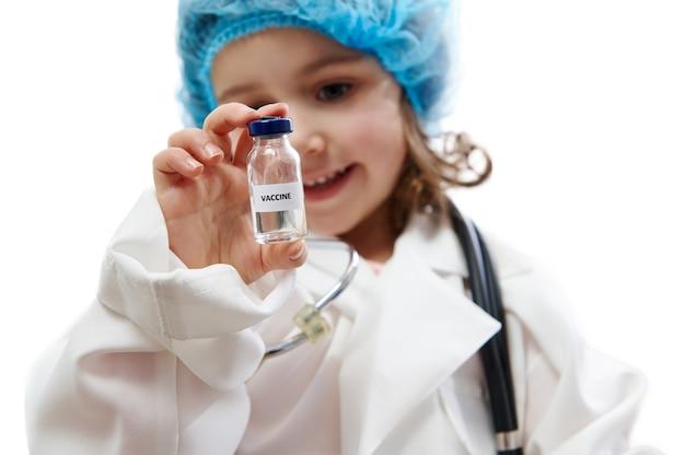 Całkiem mała dziewczynka w mundurze lekarza patrząc na fiolkę ze szczepionką na dłoni