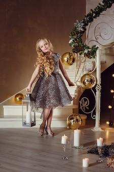 Całkiem mała dziewczynka w pobliżu drzewa nowego roku. piękna dziewczyna w sukience w pobliżu choinki czeka na wakacje. wnętrze z dekoracjami świątecznymi.
