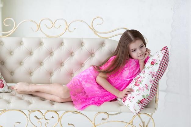 Całkiem mała dziewczynka w różowej sukience księżniczki na białej kanapie