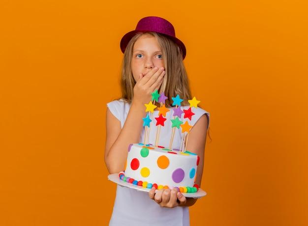 Całkiem mała dziewczynka w świątecznym kapeluszu trzyma tort urodzinowy, będąc zaskoczony, koncepcja przyjęcia urodzinowego