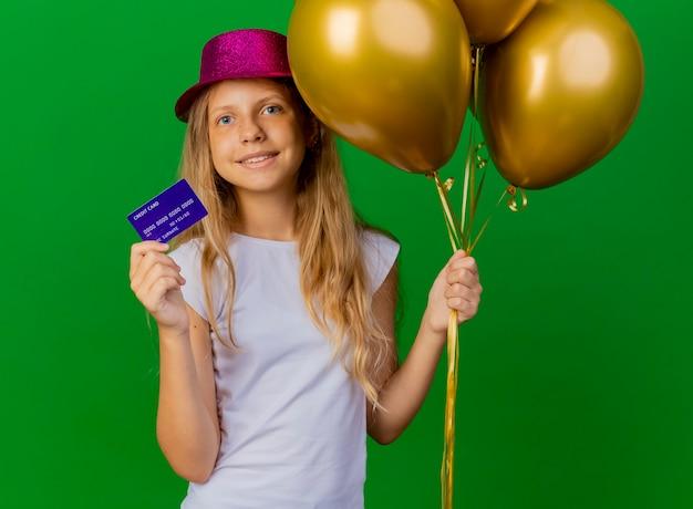 Całkiem mała dziewczynka w świątecznym kapeluszu, trzymając pudełka
