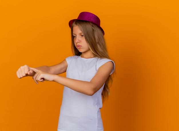 Całkiem mała dziewczynka w świątecznym kapeluszu wskazująca na jej rękę, przypominająca o niezadowoleniu czasu, koncepcja przyjęcia urodzinowego