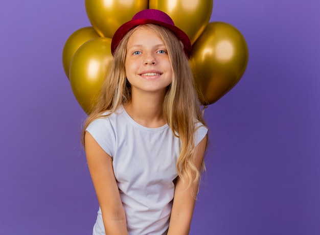 Całkiem mała dziewczynka w świątecznym kapeluszu z bukietem balonów patrząc na kamery, uśmiechnięta radośnie i pozytywnie, koncepcja przyjęcia urodzinowego stojąca na fioletowym tle
