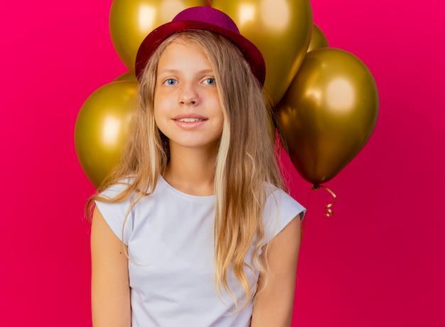 Całkiem mała dziewczynka w świątecznym kapeluszu z bukietem balonów, uśmiechając się radośnie