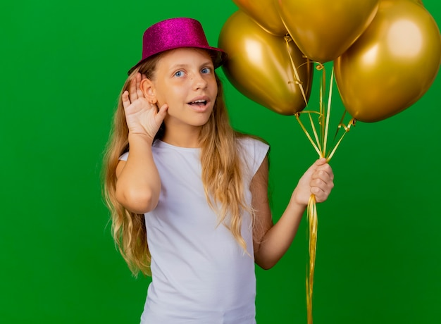 Całkiem mała dziewczynka w świątecznym kapeluszu z bukietem balonów