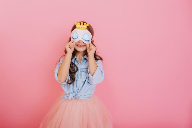 Całkiem mała dziewczynka z długimi brunetkami w tiulowej spódnicy, trzymając maskę do spania z niebieskimi oczami i złotą koroną na białym tle na różowym tle. świętujemy urodziny, bawimy się na karnawale dla dzieci
