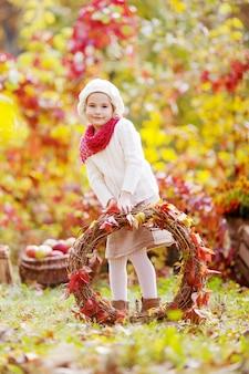 Całkiem mała dziewczynka z wieńcem czerwonych liści winogron w parku jesienią.