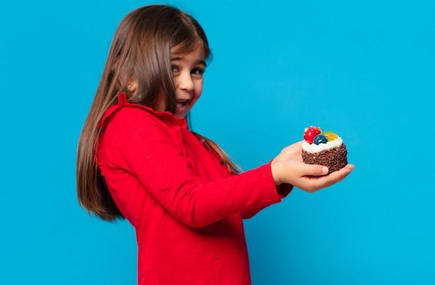 Całkiem mała dziewczynka zaskoczona wyrazem twarzy i trzymająca ciasto z filiżanką