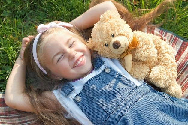 Całkiem małe dziecko dziewczynka ustanawiające z jej zabawką pluszowego misia na kocu na zielonej trawie latem uśmiechający się szczęśliwie.