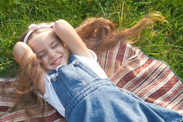 Całkiem małe dziecko dziewczynka z zamkniętymi oczami ustanawiające na koc na zielonej trawie latem drzemkę.