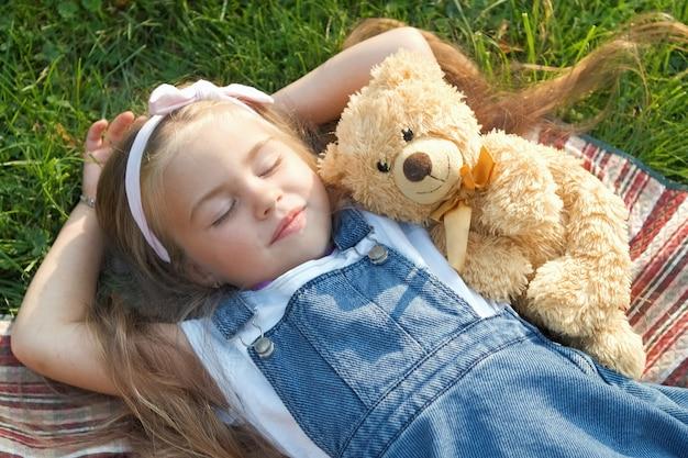 Całkiem małe dziecko dziewczynka z zamkniętymi oczami ustanawiające z jej zabawką pluszowego misia na kocu na zielonej trawie w lecie drzemał.