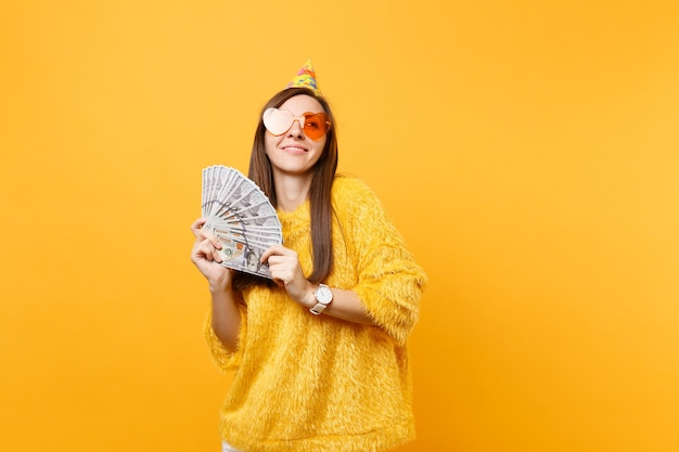 Całkiem marzycielski młoda kobieta w pomarańczowym sercu okulary urodziny party kapelusz patrząc trzymając pakiet wiele dolarów gotówki obchodzi na białym tle na żółtym tle. ludzie szczere emocje, styl życia.