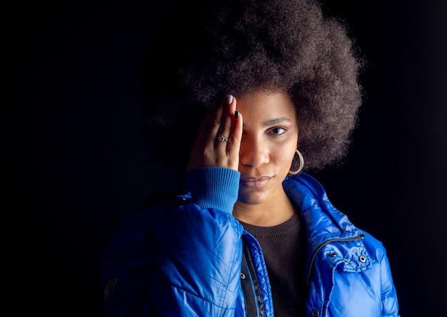 Całkiem mieszana afro kobieta, zakrywająca dłonią pół twarzy i oczu, ciemna powierzchnia