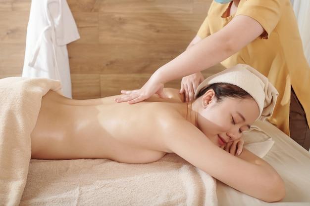 Całkiem młoda azjatka dostaje relaksujący masaż pleców z olejkami w salonie spa