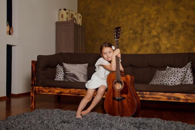 Całkiem młoda czteroletnia dziewczyna z gitarą, siedząc na kanapie we wnętrzu pokoju. szczęśliwe dziecko w domu. pojęcie domu nauki lub gry na gitarze w domu. przestrzeń praw autorskich dla witryny lub banera