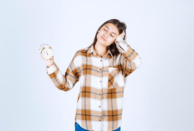 Całkiem młoda dziewczyna model trzyma budzik.