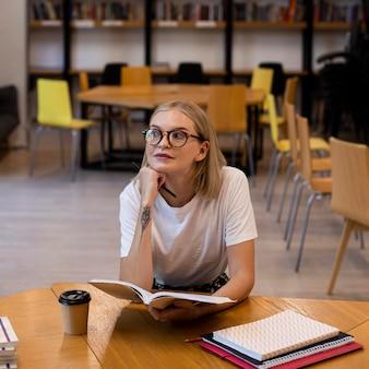 Całkiem młoda dziewczyna myśli w bibliotece