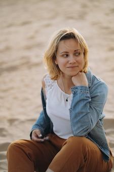 Całkiem młoda kaukaska uśmiechnięta kobieta ciesząca się słońcem na plaży o zachodzie słońca