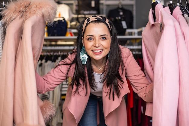 Całkiem młoda kobieta ciesząca się i bawiąca się z zakupami w sklepie lub butiku, portret w sklepie