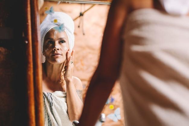 Całkiem młoda kobieta nakłada krem do pielęgnacji skóry na twarz z ręcznikami na ciało i głowę przed lustrem w domu. pozytywność ciała i troska o ludzi. piękna pani dbająca o aktywność kosmetyczną