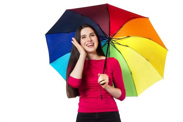 Całkiem młoda kobieta pod kolorowym parasolem, na białym tle