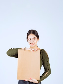 Całkiem młoda kobieta trzyma papierową torbę na białym tle.