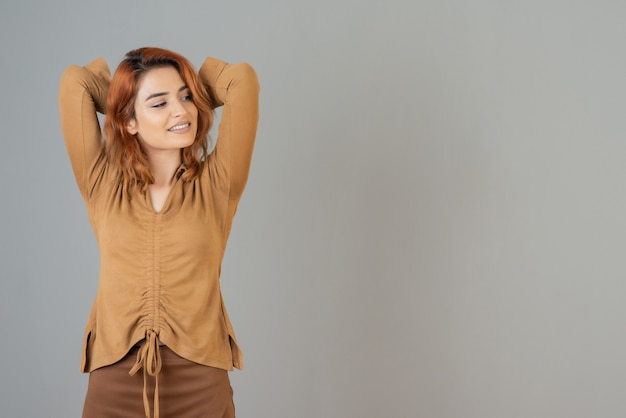 Całkiem młoda kobieta trzyma ręce w górze i uśmiecha się, odwracając wzrok