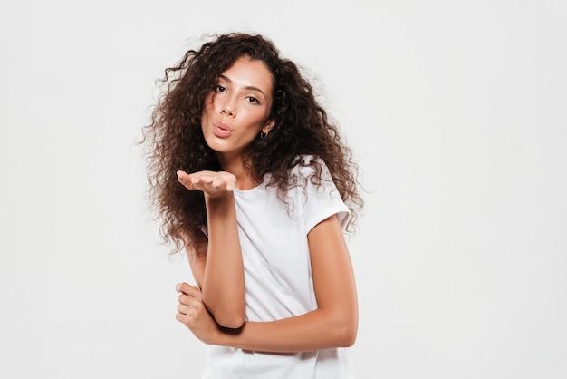 Całkiem młoda kobieta z kręconymi włosami wysyłanie pocałunek powietrza