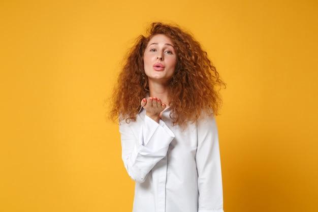 Całkiem młoda ruda kobieta dziewczyna w dorywczo białej koszuli pozuje na żółto pomarańczowej ścianie