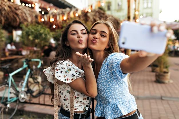 Całkiem młode, atrakcyjne dziewczyny całują się i robią selfie w dobrym nastroju na zewnątrz