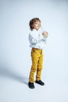 Całkiem młody chłopak w zwykłych ubraniach na białym
