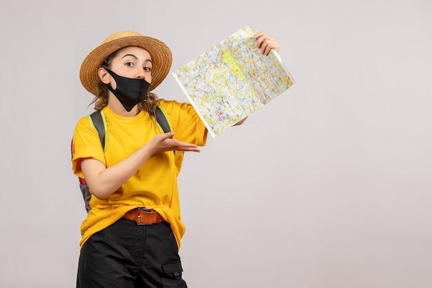 Całkiem młody podróżnik z plecakiem trzymającym mapę na szaro