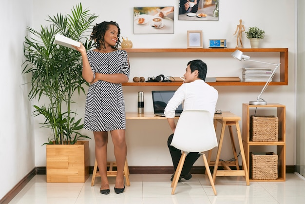 Całkiem piękna młoda czarna kobieta z książką w ręku, patrząc na współpracownika siedzącego przy biurku i pracującego nad projektem