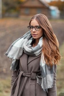 Całkiem piękna młoda kobieta model w okularach w płaszczu w szalik z dzianiny w stylu vintage cieszy wypoczynek na wsi. bardzo modna dziewczyna stoi w polu i uśmiecha się. modne jesienne ubrania damskie