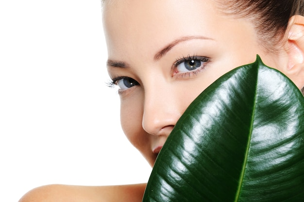 Całkiem piękna twarz kobiety za dużym zielonym liściem