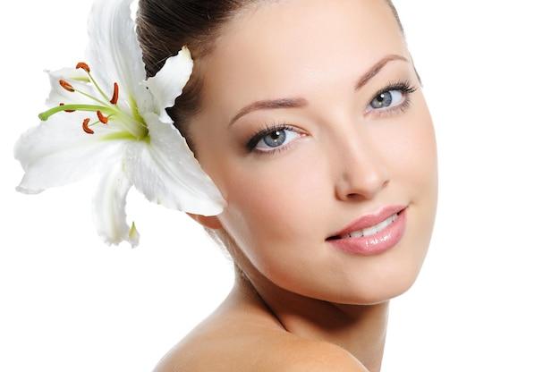 Całkiem piękna twarz kobiety ze skórą zdrowia i białą lilią we włosach