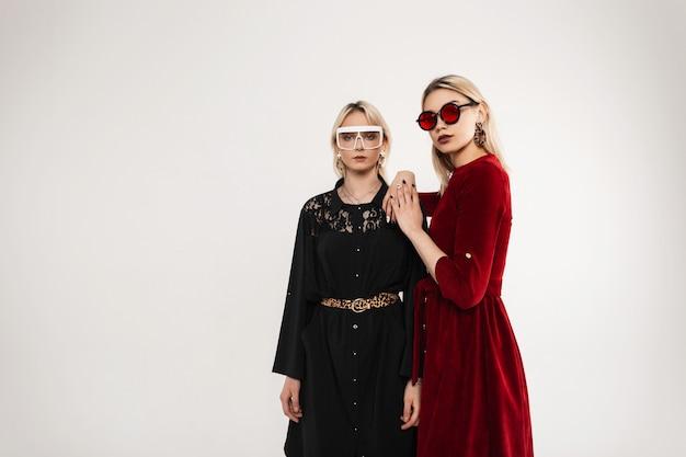 Całkiem piękne seksowne modne młode kobiety z modnymi okularami przeciwsłonecznymi noszącymi sukienkę w stylu vintage w pokoju