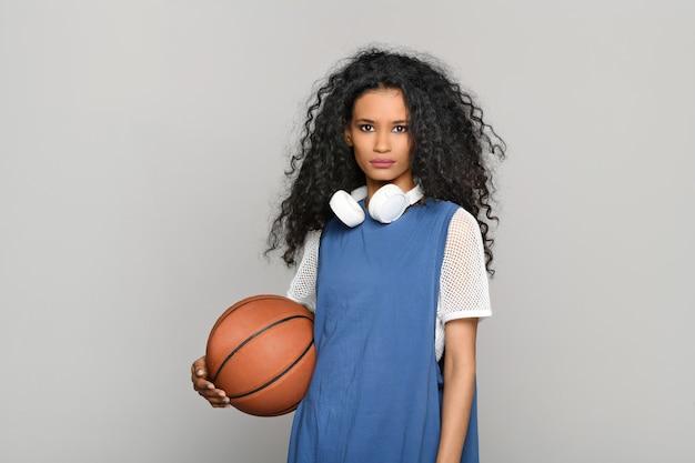 Całkiem poważna młoda dziewczyna dominikany stojąca trzymając piłkę do koszykówki, patrząc w zamyśleniu w kamerę ze słuchawkami stereo na szyi