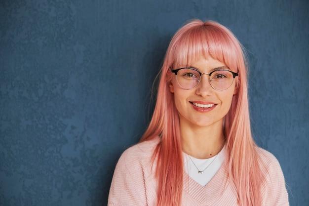 Całkiem pozytywna dama w okularach w stylowym swetrze stoi przy niebieskiej ścianie